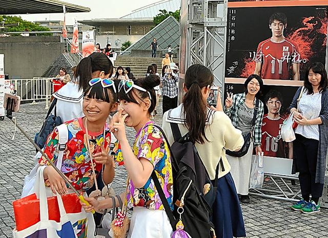 会場そばでポスターを撮影するファン。一番人気は石川祐希選手(11)だった=東京都渋谷区