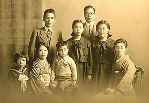 4歳の頃。制服姿の姉3人らと。左側が父、樋口盛一さんと母、郁子さん。「弟の龍雄はまだ生まれていないんです」=本人提供