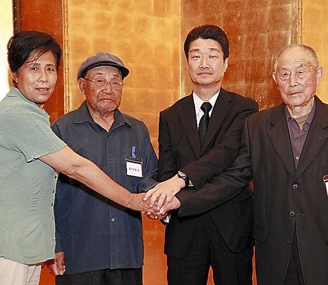 1日、北京であった和解合意書の調印式で手を握る三菱マテリアル幹部(右から2人目)と中国人の元労働者やその遺族=中国側原告団の関係者提供