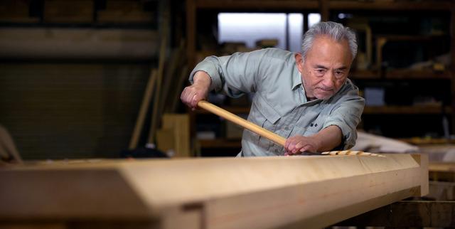 槍鉋(やりがんな)をかけるときも一心不乱。木の表面に波打ったような表情がつく=栃木県塩谷町の鵤工舎