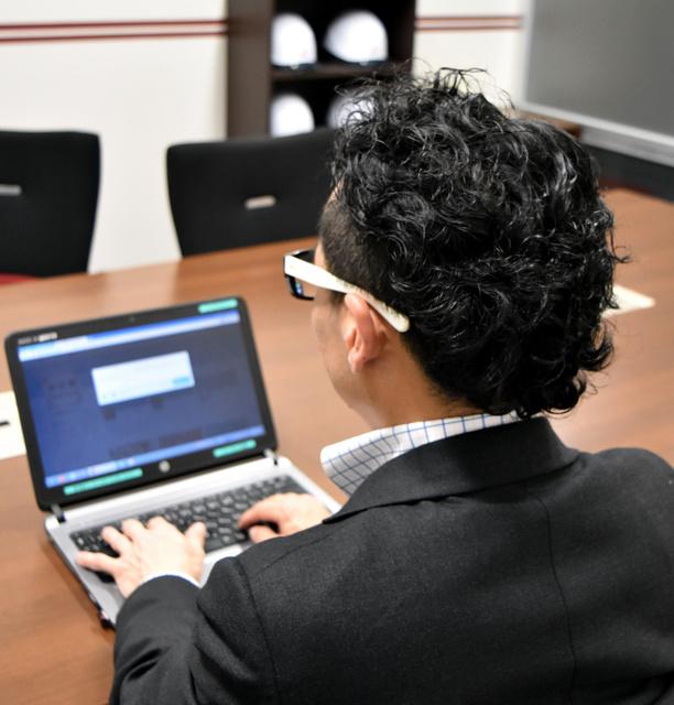 担当の男性社員は、パソコンとスマホを使ってツイートする=津市高茶屋7丁目の井村屋本社