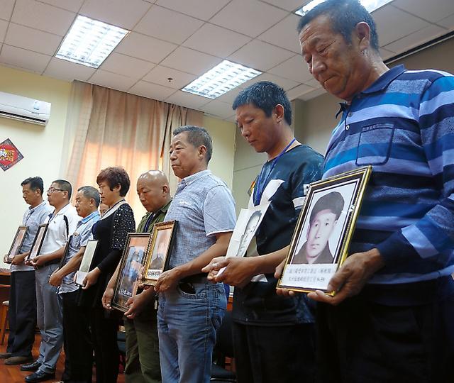 北京市内で2日、記者会見場で黙祷(もくとう)する元労働者の遺族たち=西村大輔撮影