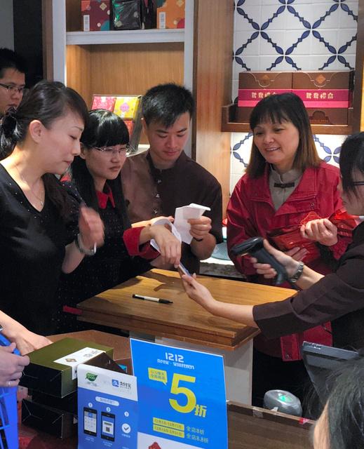 中国本土からの旅行客でにぎわうマカオ特別行政区の菓子店で、客のスマホからアリペイの支払い情報を読み取る店員(右)=マカオ市内