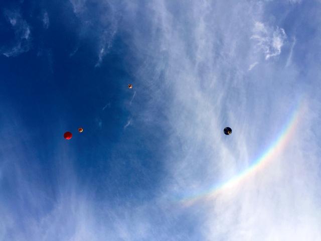 環天頂アークとみられる虹色の弧のそばを舞い上がる熱気球=佐賀市の嘉瀬川河川敷