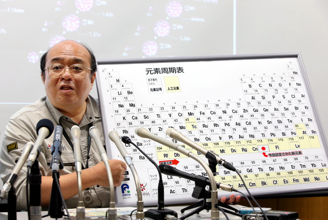 会見で元素周期表を手にする森田浩介九州大教授=9日午前11時5分、埼玉県和光市、関田航撮影