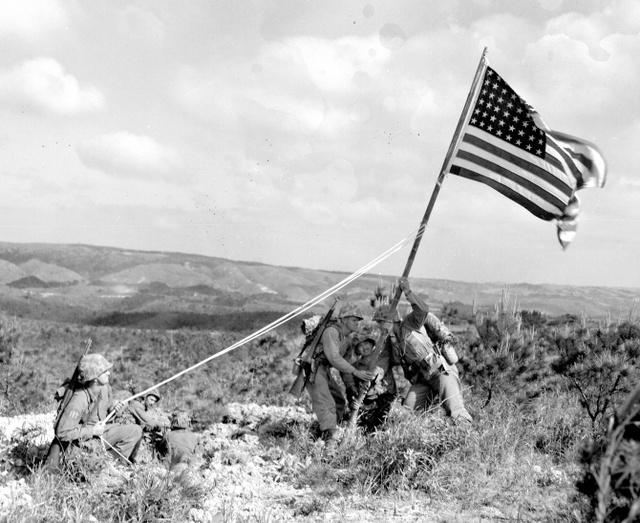 写真説明には「沖縄に掲げられた最初の星条旗」と書かれている(1945年4月19日撮影、沖縄県公文書館提供)