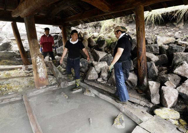 露天風呂の状態を確認する、(左から)次男の河津謙二さん、長男の誠さん、三男の進さん。地震の影響で江戸時代の石垣(右)が崩れ、屋根を支える柱が傾いた=7日午前、熊本県南阿蘇村、福岡亜純撮影