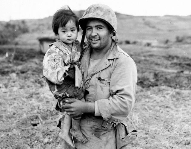 日本軍の狙撃班が使っていた壕を米海兵隊員が攻撃した際、けがをした地元の少女。薬剤師助手の米兵が保護した際の写真という(1945年5月10日撮影、沖縄県公文書館提供)