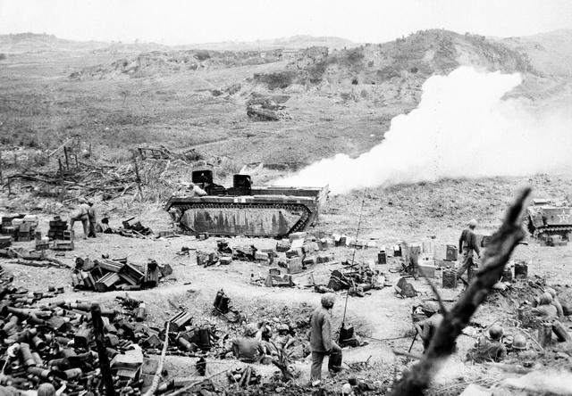 散乱したがれき、器具類や兵士たちをシュガーローフ・ヒルから見下ろす。後方で投げ込まれた手投げ弾が炸裂(さくれつ)した(1945年5月23日撮影、沖縄県公文書館提供)