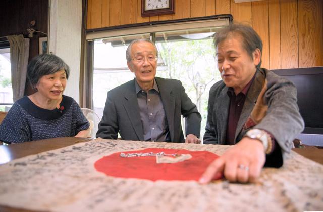 日章旗を囲んで語り合う大里一生さん(中央)と君代さん(左)、池谷進さん=志免町桜丘1丁目