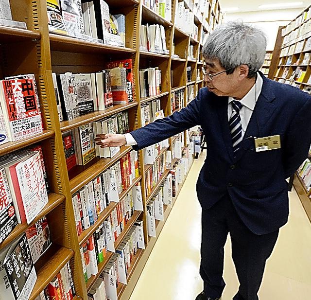 売り場を回る福嶋聡さん。「書店は民主主義を支える場。気に入らない本は排除するという選択肢はない」=大阪市のジュンク堂書店難波店