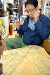 店内で古地図を広げ、漫画と地域の歴史について語る小出幹雄さん=東京都豊島区