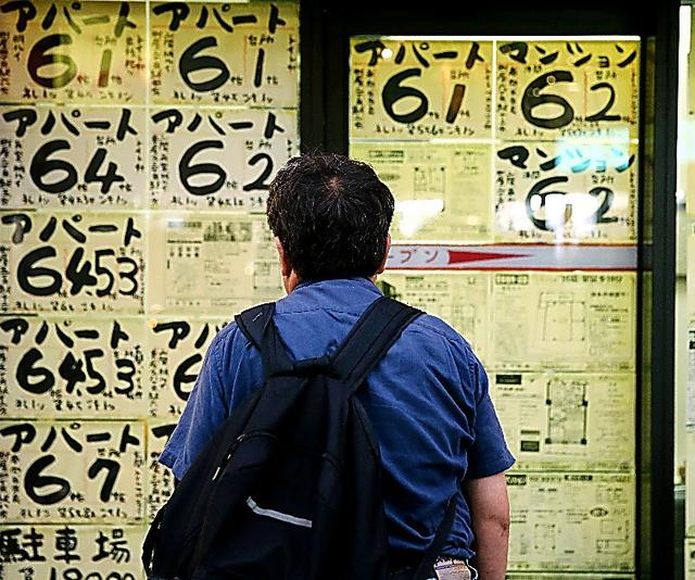 少しでも安い部屋を探そうと、不動産屋の前で足をとめる警備員の男性=13日夕、東京都内