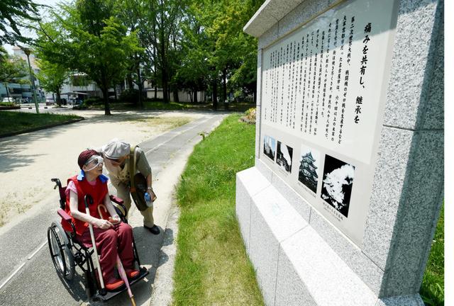 名古屋市が2014年に設置した「民間戦災傷害者の碑」を見る杉山千佐子さん。全傷連の運動経緯も紹介する異例の碑だ=2015年7月31日、名古屋市千種区の千種公園、小川智撮影