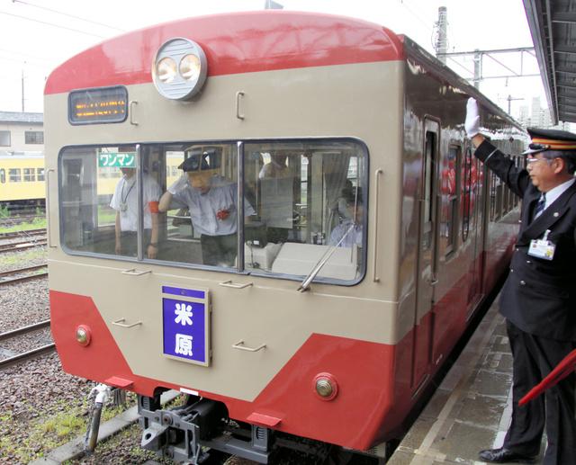 彦根駅を出発する復刻「赤電」。運転台から敬礼を返すのは三日月知事=近江鉄道彦根駅