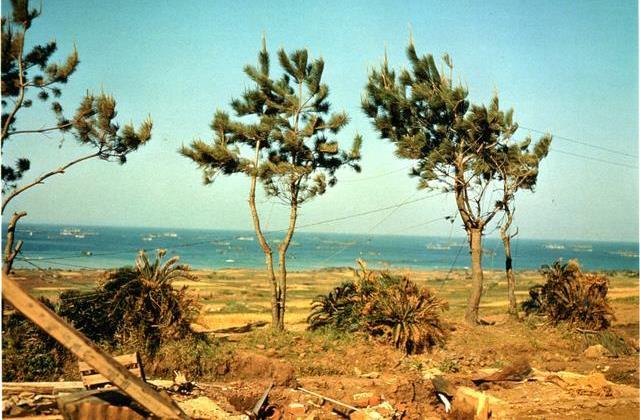 海上に米艦隊が並び、侵攻する様子。陸側からとらえたカラー写真が残る(沖縄県公文書館提供)