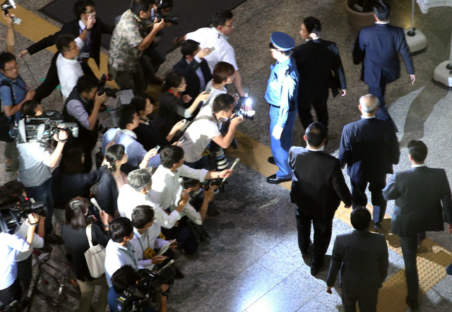 東京都庁を出る舛添要一知事(右中央)を取材する報道関係者=14日夜、川村直子撮影