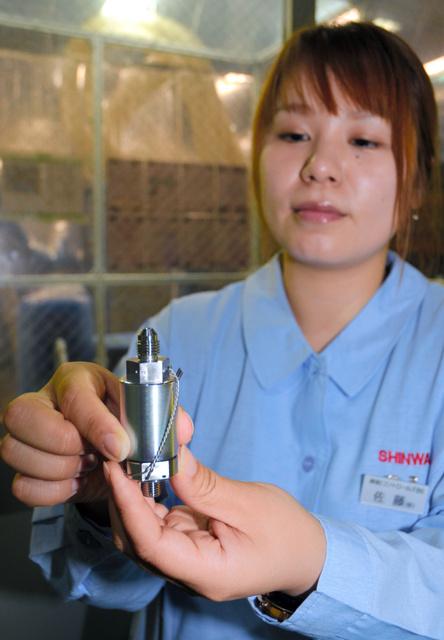 宇宙から地球に帰還する小型回収カプセルの姿勢制御用バルブに使われる電磁弁。手にしている佐藤奈美さんは23人が働く機器製造課のリーダーだ=伊那市高遠町