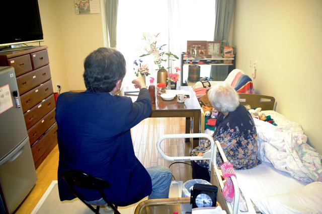 認知症の女性(右)が入居する特養の利用料は昨夏から月7万円ほど値上がりした。夫は「どうしていきなり倍になるのか。納得できない」と話す=金沢市