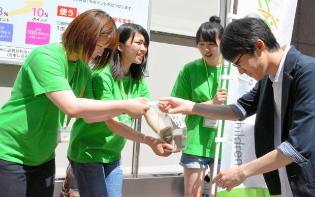 通行人から寄付を受け取る千葉碧さん(左から2人目)=仙台市青葉区