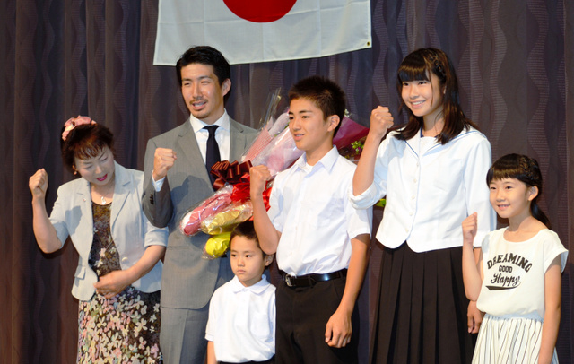 花束を贈られ、おい、めいらと笑顔でポーズを取る渡辺一成選手(左から2人目)=いわき市植田町