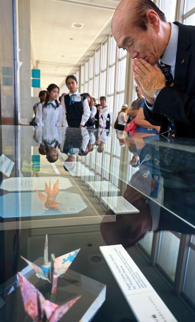 オバマ米大統領がつくった折り鶴に手を合わせる佐々木雅弘さん=18日午後2時47分、広島市中区の平和記念資料館、宮崎園子撮影