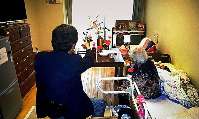 認知症の女性(右)が入居する特養の利用料は昨夏から月7万円ほど値上がりした=金沢市