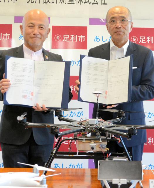 ドローンを前に協定書を取り交わした和泉聡市長(左)と晃洋設計測量の蓼沼恒男社長=20日、足利市役所