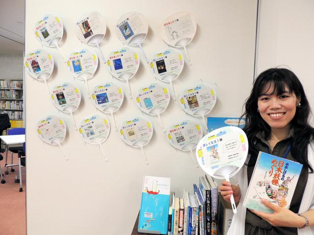 手づくりうちわとお薦め本を手にする稲葉裕美さん=刈谷市の愛教大付属図書館