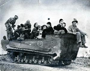 避難先から米軍車両で村に帰る女性や子どもたち。沖縄戦「終結」後の写真とみられる(1945年、米軍撮影)