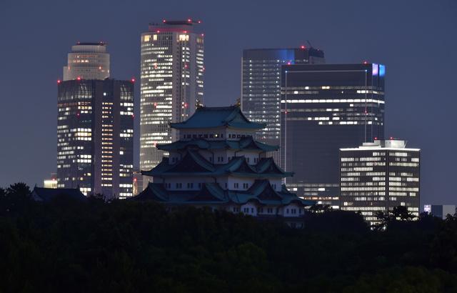 名古屋駅前の高層ビル群を背に、ライトダウンされた名古屋城=21日午後、戸村登撮影