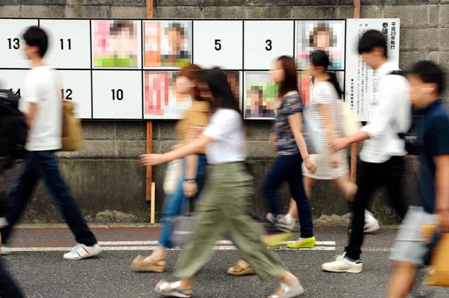 選挙ポスターが貼られた掲示板の前を通学する学生たち=22日午前10時26分、大阪府東大阪市、森井英二郎撮影