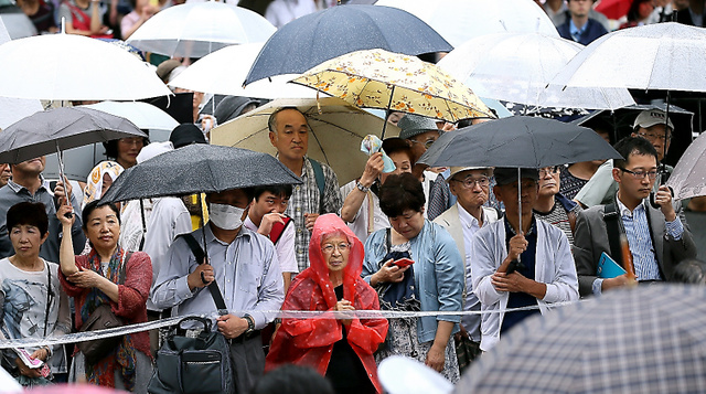 第一声に耳をかたむける有権者ら=22日午前、東京・新宿、岩下毅撮影
