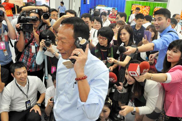 株主総会後にシャープのロボット型電話「ロボホン」を耳に当ててPRする鴻海精密工業の郭台銘会長=22日午後、台湾・新北市、新宅あゆみ撮影