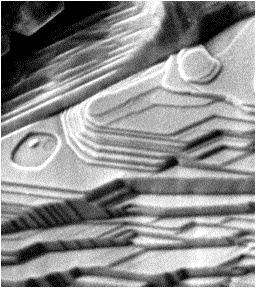 イトカワで採取された微粒子の表面。より大きな天体の一部だった約45億年前に、熱で温められた後に冷やされ、結晶化した跡(JAXA提供)
