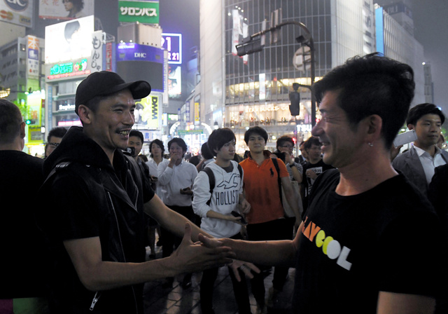 改正風営法が施行され、JR渋谷駅前で関係者と喜ぶZeebraさん(左)=23日午前0時すぎ、東京都渋谷区、竹花徹朗撮影