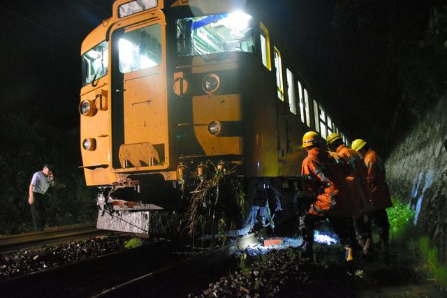 土砂に乗り上げ、脱線した列車を調べる関係者=23日午前2時1分、広島市安芸区、清水康志撮影