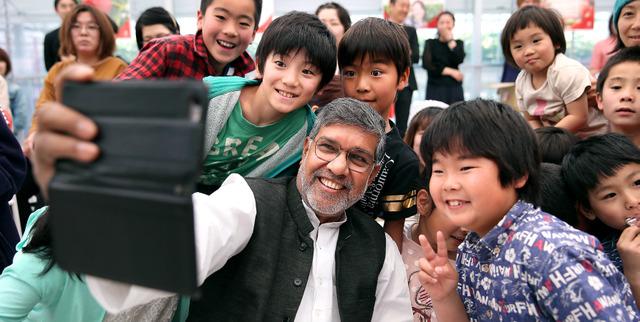 講演会に集まった子どもたちの輪に入り、自身のスマートフォンでカシャ! あっという間にみんなと打ち解けた=宮城県山元町