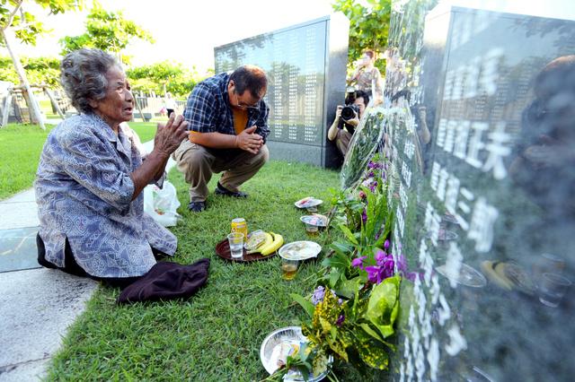名前が刻まれた「平和の礎」に向かい手を合わせる人たち=23日午前7時5分、沖縄県糸満市、小宮路勝撮影