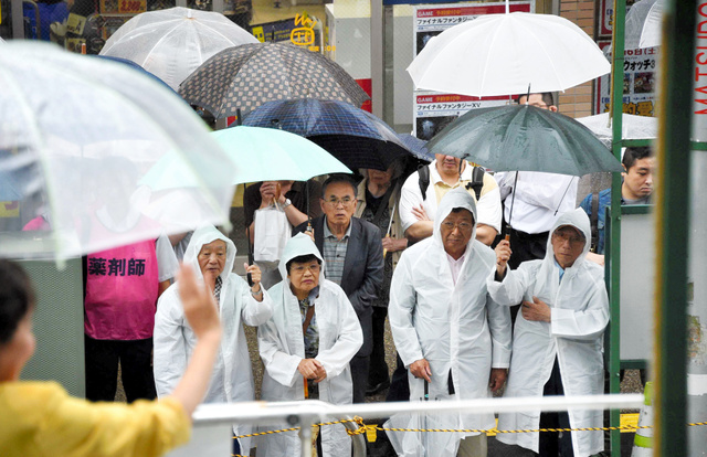 雨の中、街頭演説に集まった有権者ら=23日午前10時51分、千葉県内、恵原弘太郎撮影