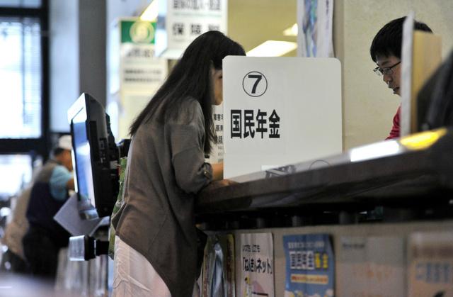 市役所を訪れ、国民年金と国民健康保険の保険料減免を相談する女性(左)=6月13日、埼玉県内、仙波理撮影