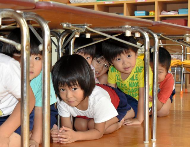 「地震です!」の声にすかさず机の下に隠れた子どもたち=紀美野町神野市場