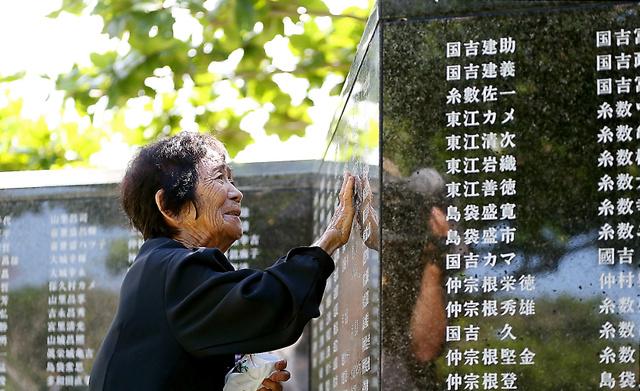 「平和の礎」に刻まれた兄の名に手を触れ涙を流す遺族=23日午前9時22分、沖縄県糸満市、小宮路勝撮影