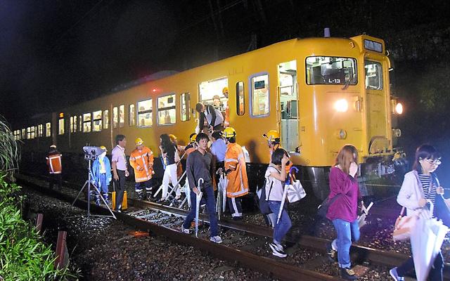 脱線した電車から疲れた表情で降り、バスに向かう乗客ら=23日午前3時、広島市安芸区、清水康志撮影