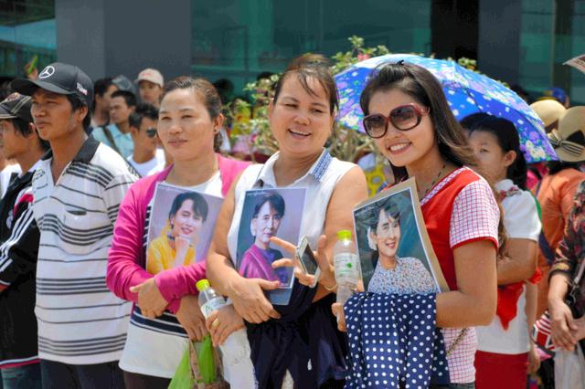 肖像写真を胸にスーチー氏の到着を待つ、ミャンマー人移民労働者たち=23日午後、タイ中部サムットサコン県、大野良祐撮影