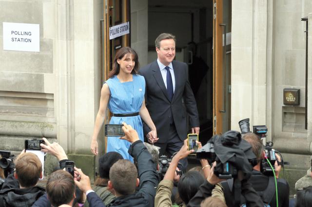 ロンドンで23日、投票を終え、妻と投票所を後にするキャメロン首相=AP