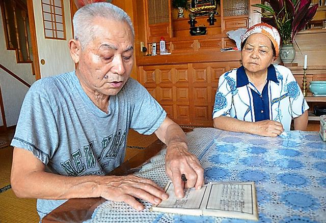 沖縄戦で亡くなった家族の享年などが書かれた過去帳を見る親富祖清武さん(左)と妻のハツ子さん=沖縄県浦添市