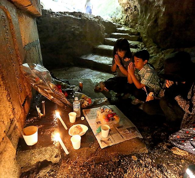 沖縄師範学校の学徒たちが戦没した「健児の塔」下のガマ(壕〈ごう〉)では、多くの人たちが訪れ犠牲者に手を合わせていた=23日午前、沖縄県糸満市、上田幸一撮影
