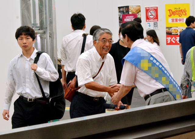 有権者と握手を交わす候補者=24日、JR浦和駅、平良孝陽撮影