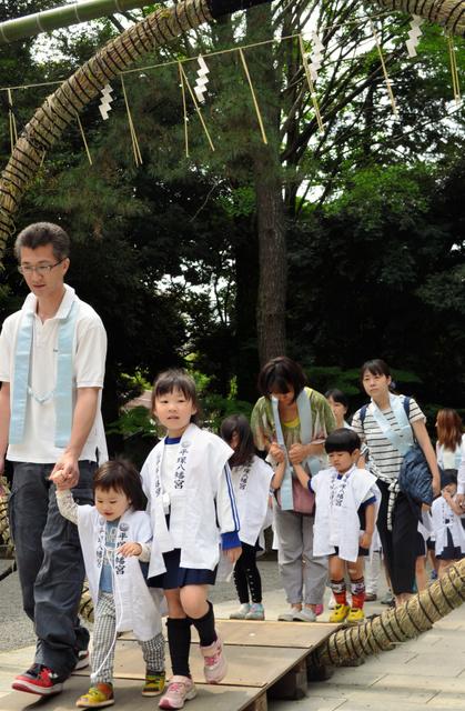 父母らに手を引かれ輪をくぐる園児ら=平塚市浅間町の平塚八幡宮